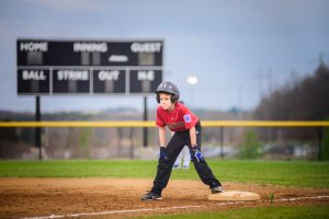 Little League Baseball player standing on first base wearing a red shirt and helmet. Loudoun County, Virginia Photographer