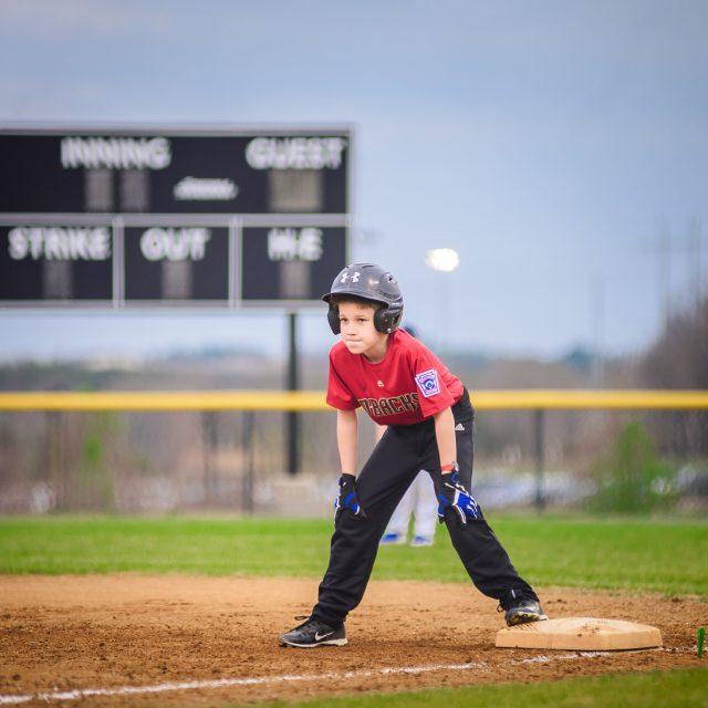 Little League Baseball player standing on first base wearing a red shirt and helmet. Loudoun County, Virginia Photographer