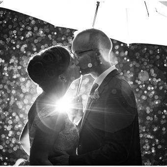 Bride and Groom kissing in the rain under an umbrella atThe Rust Manor House in Leesburg, Virginia.