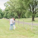 casually dressed couple standing in a green field near a wire fence.