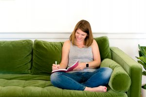 Loudoun County Wedding Photographer, Lydia Teague sits on a green couch planning.