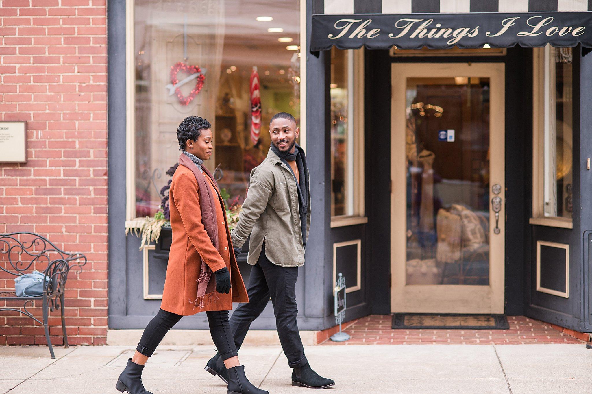 Engaged couple walking down sidewalk